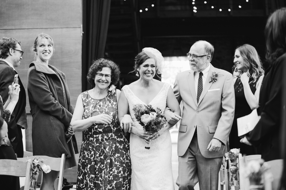 This is a photo of Rachel walking down the aisle with her parents. What a precious moment!
