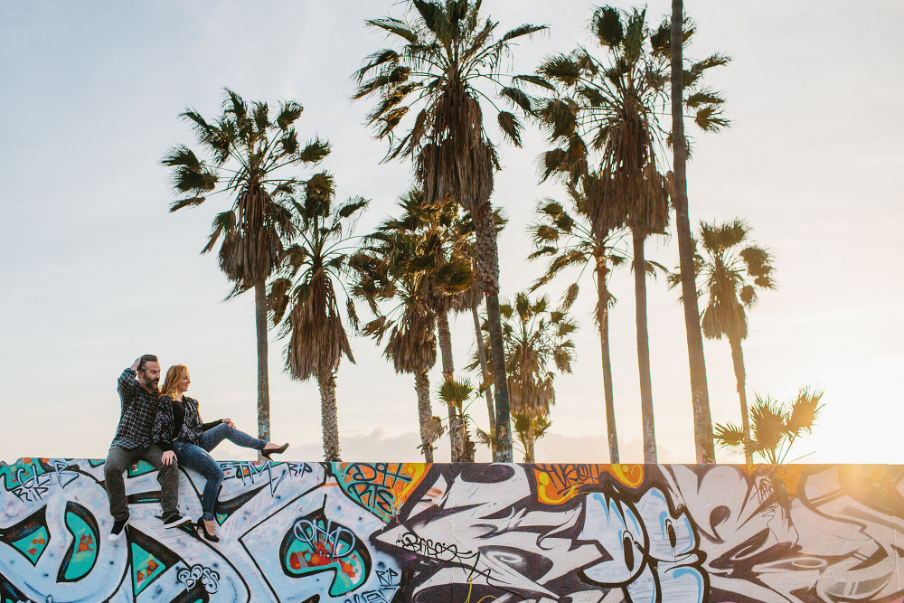 The couple sitting on a wall at the beach.