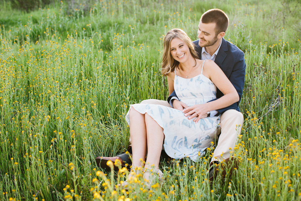 Kara and Sean sitting in a grass field.