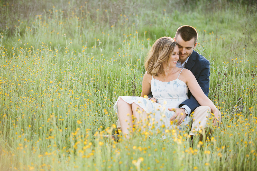 The couple in a field of yellow flowers.