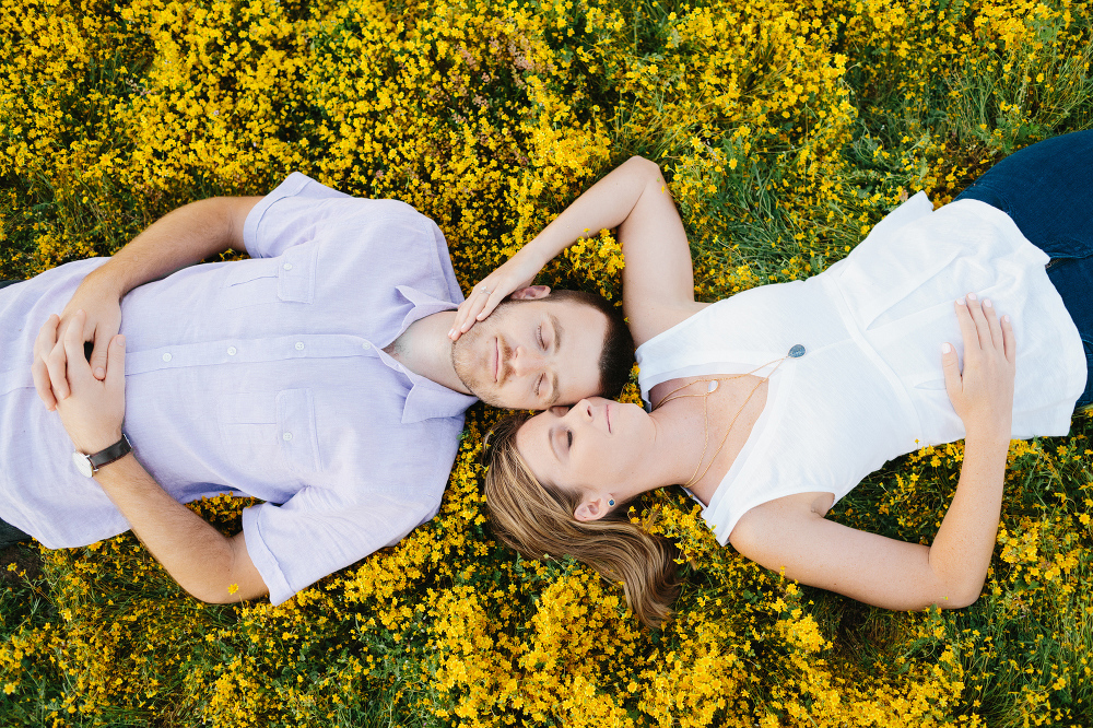 The couple laying in the yellow fields.